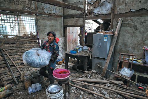 ▲昨日,双河镇,村民在破损的房间内整理物品,带走离开。