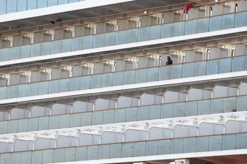 """2月6日,在日本横滨,""""钻石公主""""号邮轮上被阻隔的乘客在打电话。新华社记者杜潇逸 摄"""