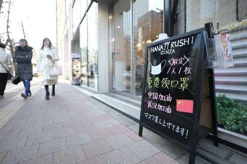 2月11日,在日本东京,银座的一个商铺门前的招牌上写着免费施舍口罩和为中国武汉添油鼓劲的内容。新华社记者 杜潇逸 摄