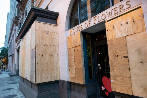 美国华盛顿,白宫附近的一家花店用木板添固了门窗。图源:新华社