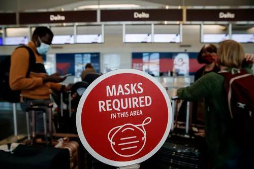 11月24日,在美国弗吉尼亚州阿灵顿的里根国家机场,戴口罩的旅客们站在一处要求佩戴口罩的标识旁。新华社发(沈霆摄)