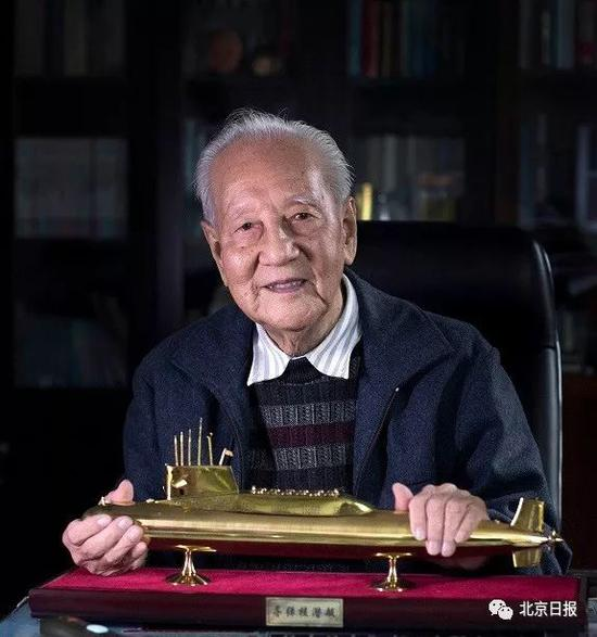 黄旭华院士手捧潜艇模型的肖像照片(2016年12月20日摄)。新华社发