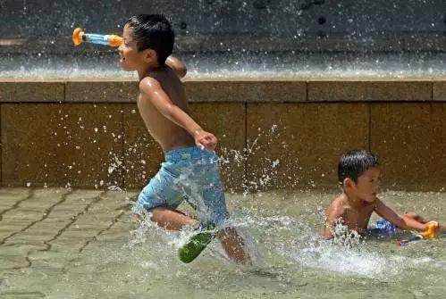 ▲原料图片:2017年7月20日,在日本东京一个公园,孩子们在喷泉池里游玩。 (新华社/法新社)