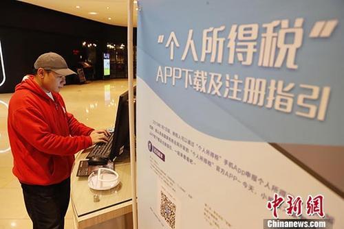 资料图:市民在位于上海市静安嘉里中心内的个人所得税基础信息采集点进行相关信息登记。 中新社记者 殷立勤 摄