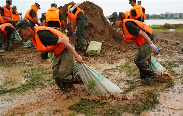 7月11日,武警战士在江西省鄱阳县鄱阳镇江家岭村搬运沙袋。新华社记者 周密 摄