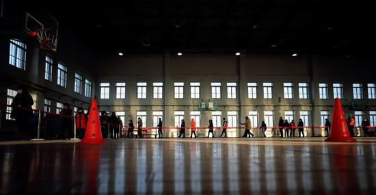 1月11日,辽宁沈阳市铁西区,人们在彰驿学校检测点排队等待核酸采样。图/新华