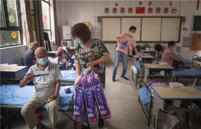 7月7日,在街道口小学东方雅园分校安置点,工作人员为武汉市洪山区天兴乡村民发放生活物资。新华社记者 肖艺九 摄