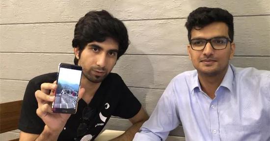帕尔特·达尔(左)和达克什·卡迪安展示他们去中国的照片。新华社记者赵旭摄