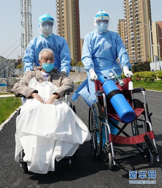 在湖北武汉,为确保患者有充足供氧,援鄂医生胡世颉(右一)推着氧气瓶,护送81岁的新冠肺炎重症患者去做CT检查(3月20日摄)。新华社记者 王毓国 摄