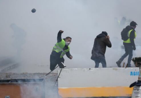 抗议者向警戒线抛掷石块 (图源:卫报)