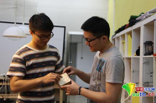 """清华大学创客空间协会成员张承巍(左)与毕滢(右)正在引见他们的创意成果""""音乐盒子""""。材料图"""