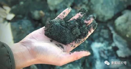 尾矿库用来筑坝的矿渣掉落在河道中,呈现蓝黑色,伴有异味。 新京报记者 游天燚 摄