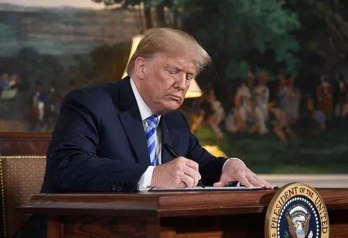 2018年5月8日,在美国华盛顿,美国总统特朗普签署关于美国退出伊核协议的文件。新华社/法新