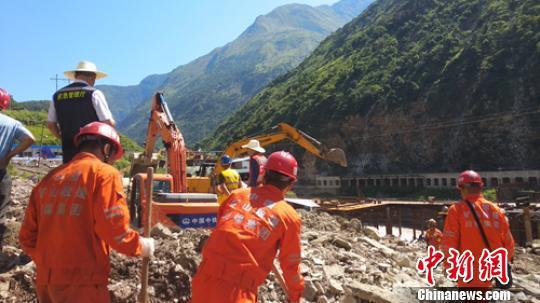 挖掘機和救援人員抵達垮塌堆積體上展開搜救。 謝培林 攝
