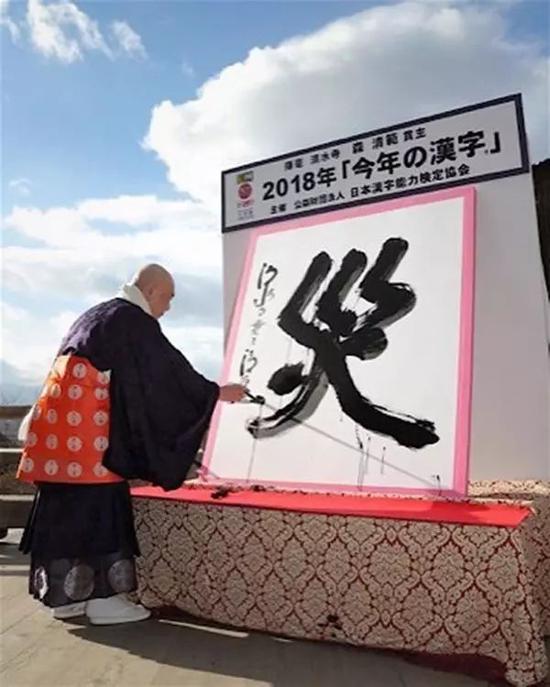"""(图为净水寺的森清范方丈挥笔写下""""灾""""字)"""