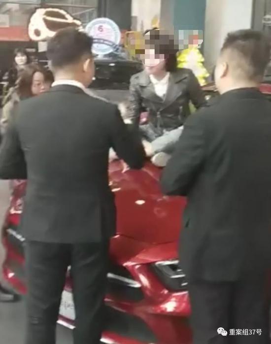 ▲女车主情绪激动地坐上奔驰车前盖与销售人员理论。受访者供图