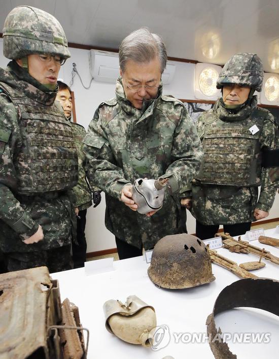 28日,文在寅视察前面哨所,翻望朝鲜搏斗士兵的遗物。(韩联社)