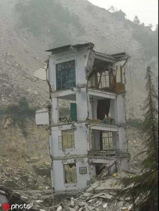 """2019-06-18,5.12大地震之后的映秀小学,只有一间课室面积的危楼还""""耸立""""在废墟上,摇摇欲坠,危楼左右两边的校舍已呈毁灭性倒塌。"""
