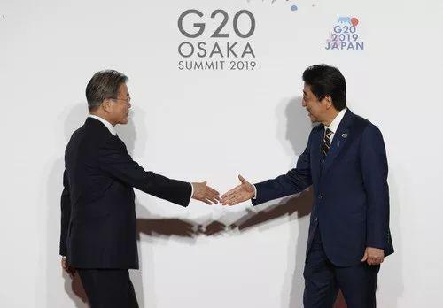 6月28日,在日本大阪,日本首相安倍晋三(右)欢迎韩国总统文在寅。新华社发