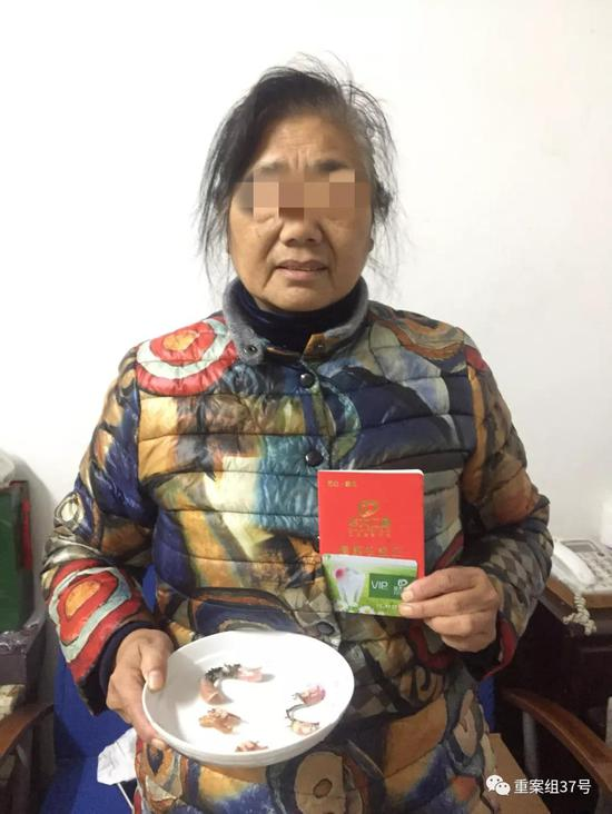12月6日,杨玉琴右手拿着近年来做过的伪牙,左手拿着华大仁通公司给她发的《健康权好证》,内里记录了她的会员等级与享福扣头。 新京报记者韩茹雪摄
