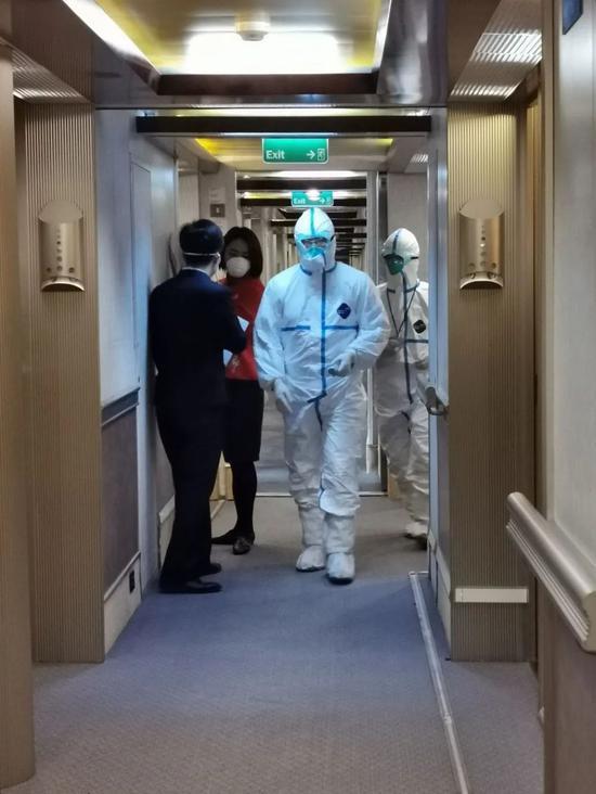 身穿防护服的做事人员上邮轮检查。受访者挑供