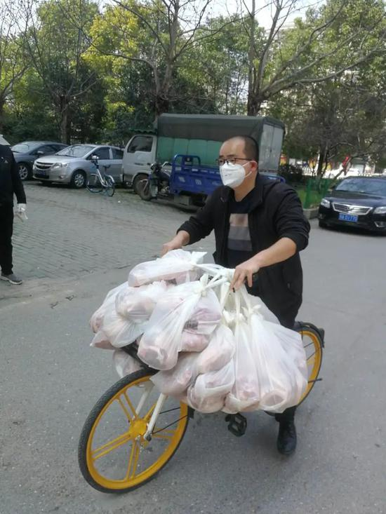 王亮在车把上挂满了冻猪肉,运输业主们的团购物资