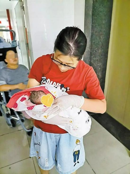 李华燕抱着新生儿准备送医检查其健康状况。受访者供图