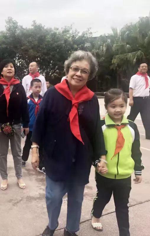 图为2018年在朱德红军小学,小朋友带着陶斯亮参观校园。