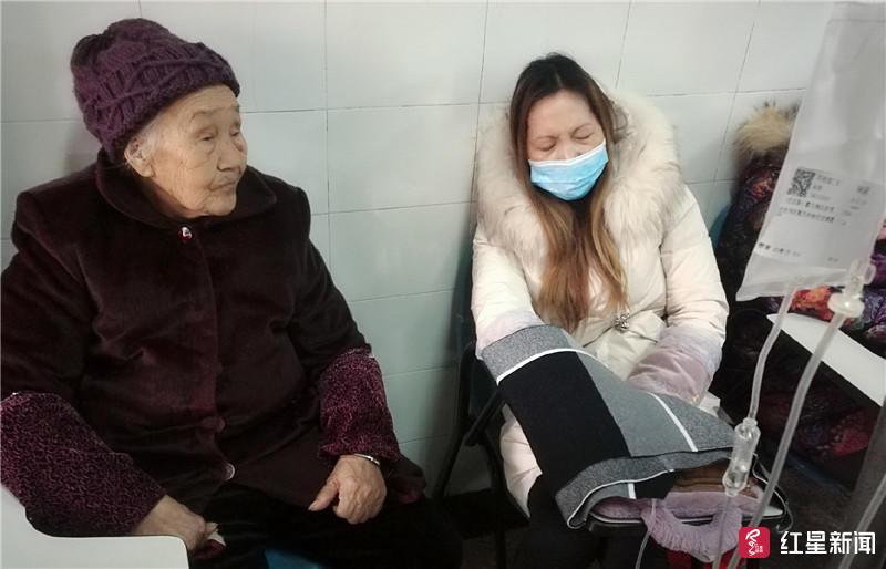 ↑邓明琼在91岁老母亲陪同下在医院输液