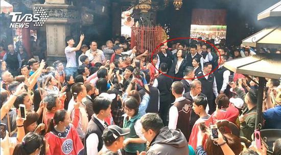 """蔡英文2月6日在多名黑衣安保人员陪同下发红包(图片来源:台湾""""TVBS"""")"""