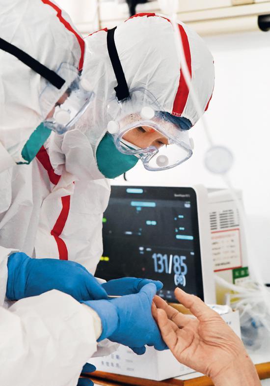 中部战区总医院感染科十病区医务人员无微不至的精心护理,赢得了患者的称赞。图为2020年2月7日上午医务人员在病房为患者采取血样进行检测。 解放军报记者 王传顺/摄