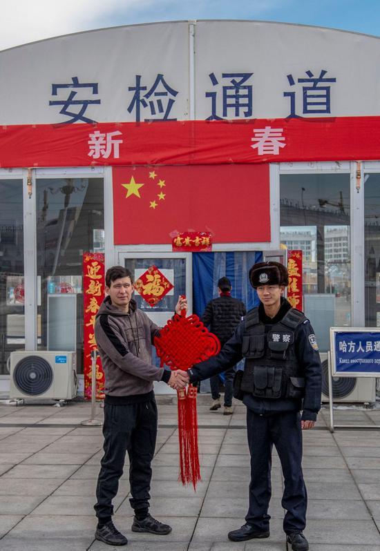 2月4日,霍尔果斯口岸边境派出所民警正在中哈霍尔果斯国际边境合作中心中方区域内向外方人员赠送中国结。郭炜 摄