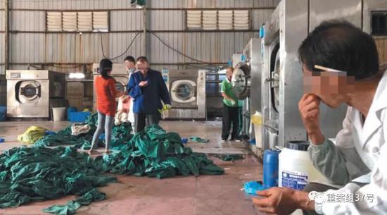 ▲11月30日,丰源洗衣中心内大量的手术布草堆在地上期待洗涤,别名身穿蓝色衣服的工人用脚踩着布草。新京报记者 尹亚飞 摄