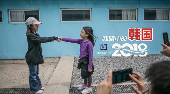 """△2018年5月5日,游客在韩国南杨州电影制片厂的复制板门店布景处拍照,""""重演""""韩朝首脑历史性会面握手转瞬。"""