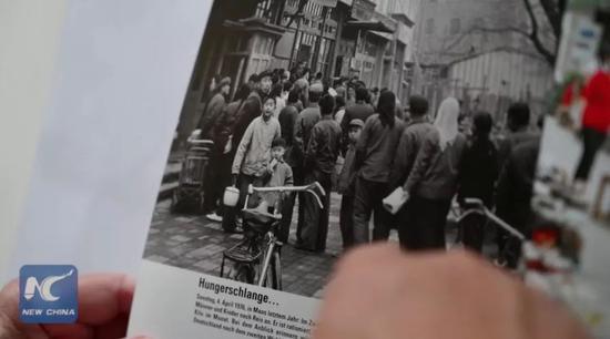▲库摩展示他1976年在中国拍摄的照片。(新华社报道截图)