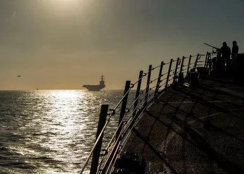 """4月13日,美国海军""""亚伯拉罕·林肯""""号航母(中)与阿里·伯克级驱逐舰""""班布里奇""""号(右)编队通过直布罗陀海峡。新华社/路透"""