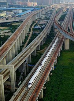 """变身开放高地 迈向""""中心城市"""",一列动车组列车驶过郑州市区(2017年8月17日无人机拍摄)新华社图"""