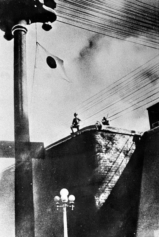 图为日军侵占沈阳城后,耀武扬威地站在城头,悬挂起日本国旗。新华社稿