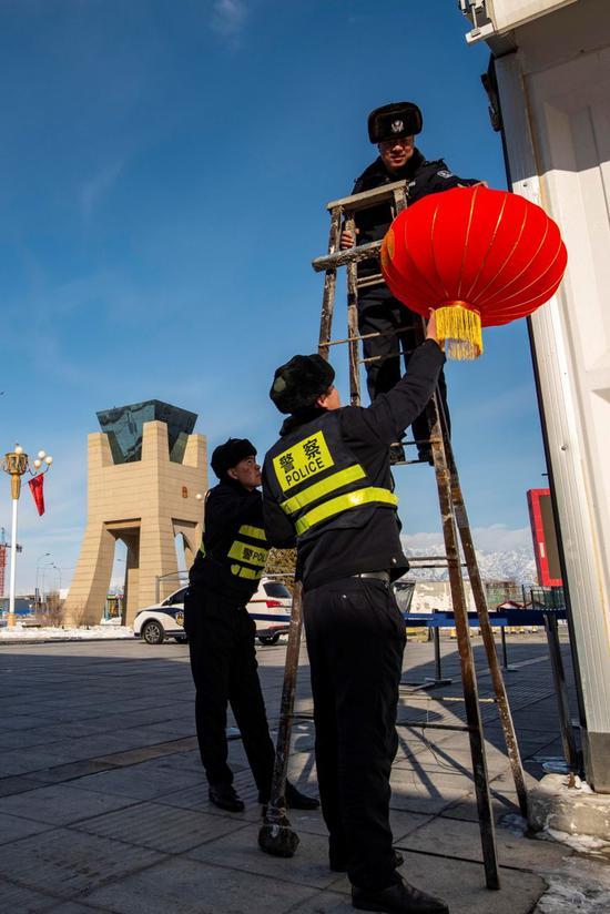 除夕当天,新疆霍尔果斯口岸边境派出所民警正在中哈霍尔果斯国际边境合作中心中方区域内悬挂红灯笼。郭炜 摄