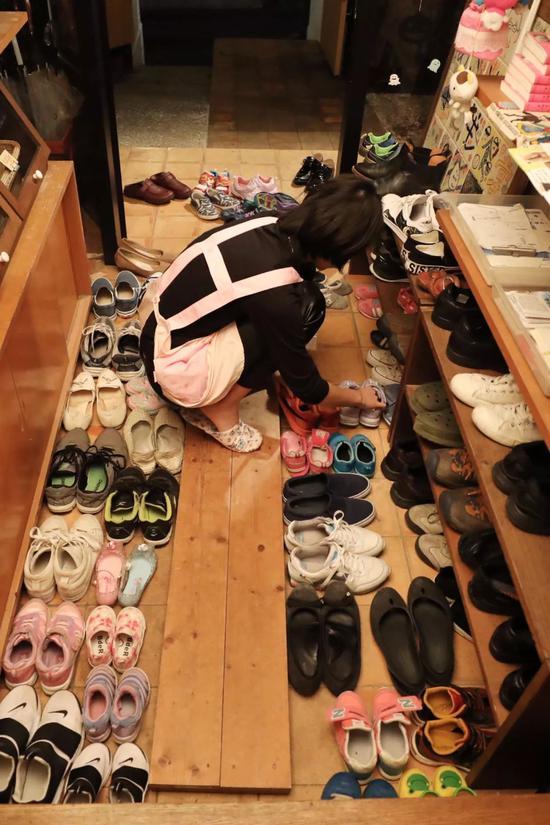 自愿者收拾门口堆满的鞋。