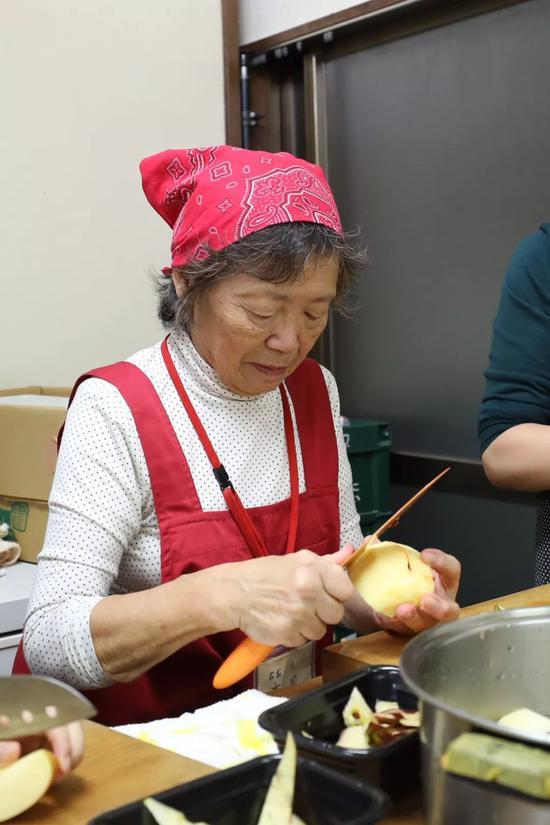 老奶奶在食堂厨房里削苹果。