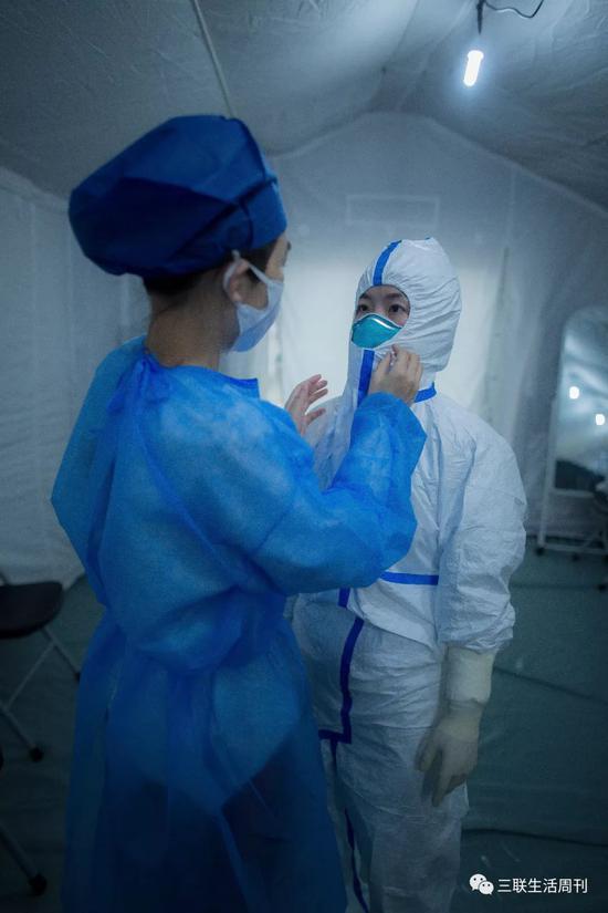 2月13日入艙前,醫護人員穿戴防護服。  黃宇 攝