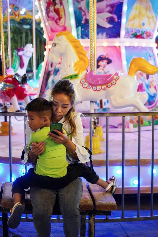 夜晚,奢香古镇外成了游乐场,一对母子在旋转木马前休息
