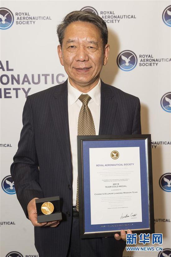 11月25日,在英国伦敦,中国探月工程总设计师、中国工程院院士吴伟仁展示奖章和证书。 英国皇家航空学会2019年度颁奖典礼25日晚在伦敦举行,嫦娥四号任务团队获得本年度团队金奖,成为本年度全球唯一获此殊荣的团队。这是英国皇家航空学会成立153年来首次向中国项目颁发奖项。 新华社发(雷伊・唐摄)