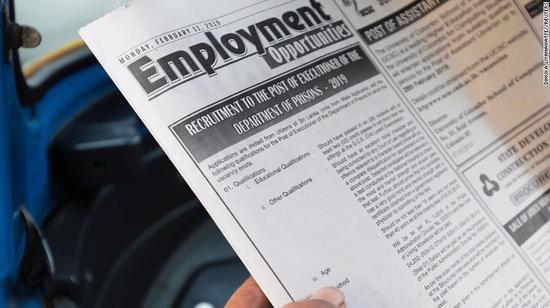 一位男士在阅读这份招聘启示。(图片:CNN)