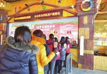 持华为手机的游客在列队购票。