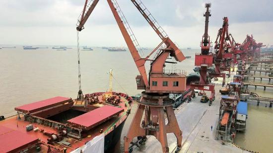▲江苏南通港码头卸运巴西进口大豆。(视觉中国)