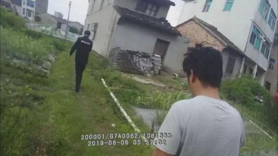 當天早上6時左右,男子(穿T恤者)被民警帶回派出所做調查。