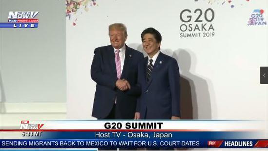 二人握着手露出笑容