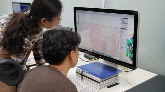 图为钞票设计师通过计算机辅助修改设计
